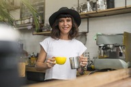Portrait of woman with black hat behind the bar preparing a coffee - SBOF01212