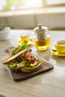Crusty bread with green salad and ham on wooden plate and green tea in cafe - SBOF01221