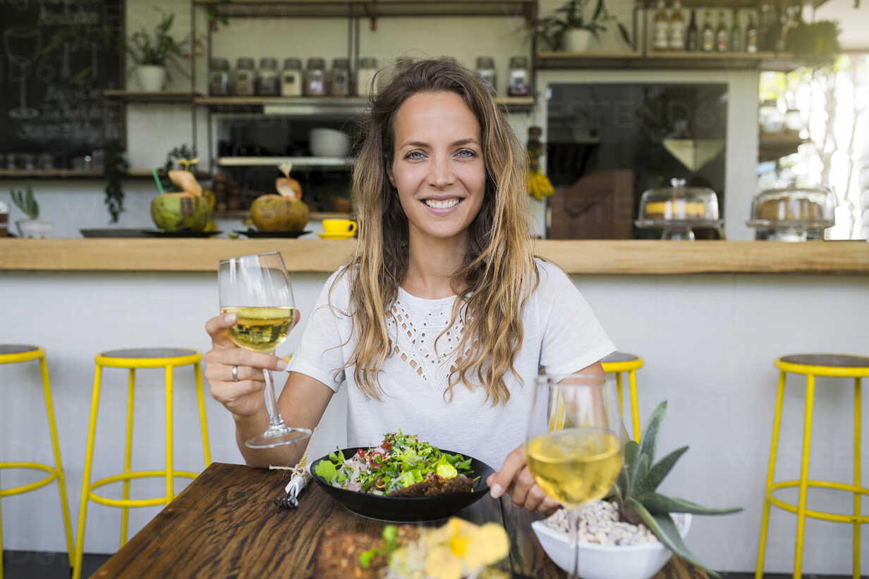 Portrait of smiling woman holding glass of wine in a cafe - SBOF01251 - Steve Brookland/Westend61