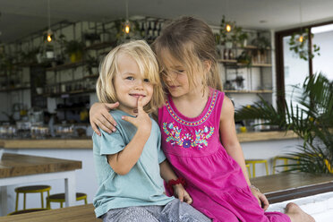 Portrait of sister hugging brother in a cafe - SBOF01254