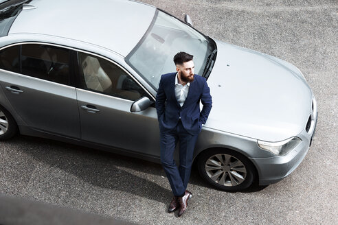 Young man wearing suit, leaning against new car - MAEF12499