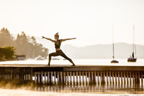Woman practicing yoga on jetty at a lake - DAWF00563