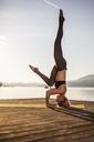 Woman practicing yoga on jetty at a lake doing a headstand - DAWF00566