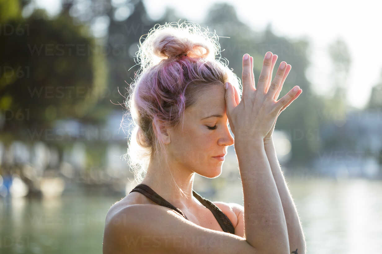 Woman with dyed hair meditating at a lake - DAWF00572 - Daniel Waschnig Photography/Westend61