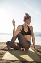 Woman sitting on jetty at a lake practicing yoga - DAWF00575