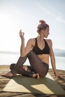 Woman sitting on jetty at a lake practicing yoga - DAWF00575