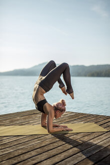 Woman practicing yoga on jetty at a lake - DAWF00578