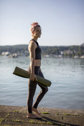 Woman in sportswear walking with yoga mat at lakeshore - DAWF00584