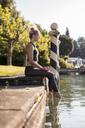 Woman in sportswear sitting at lakeshore with feet in water - DAWF00587