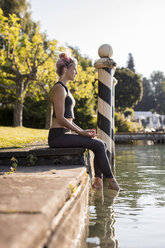 Woman in sportswear sitting at lakeshore with feet in water - DAWF00587