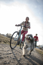 Man and woman with dog riding bicycle on dirt track - ECPF00179