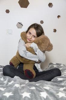 Portrait of smiling girl sitting on bed hugging teddy bear - SARF03478