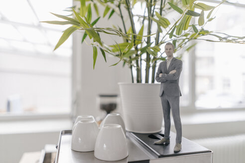 Miniature businessman figurine standing on coffee machine in office - FLAF00115