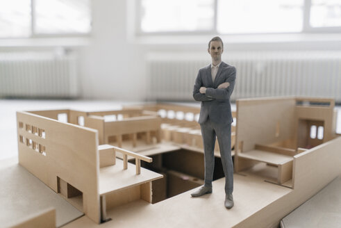 Miniature businessman figurine standing in architectural model - FLAF00118