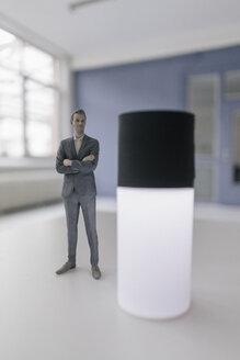 Miniature businessman figurine standing next to smart home device - FLAF00121