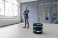 Miniature businessman figurine standing next to smart home loudspeaker - FLAF00124