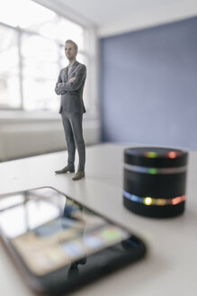Miniature businessman figurine standing next to smart home loudspeaker and smartphone - FLAF00127