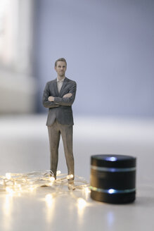 Miniature businessman figurine standing next to smart home loudspeaker with chain of lights - FLAF00130