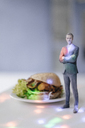 Miniature businessman figurine standing next to fast food surrounded by points of light - FLAF00139