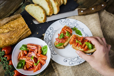 Taking bruschetta, white bread with tomato and olive oil - GIOF03765