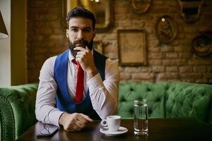 Portrait of fashionable young man sitting on couch in a cafe - ZEDF01098