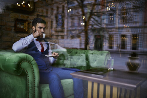 Fashionable young man sitting on couch in a cafe drinking coffee - ZEDF01101