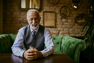 Portrait of elegant senior man sitting on couch in a cafe smiling - ZEDF01104