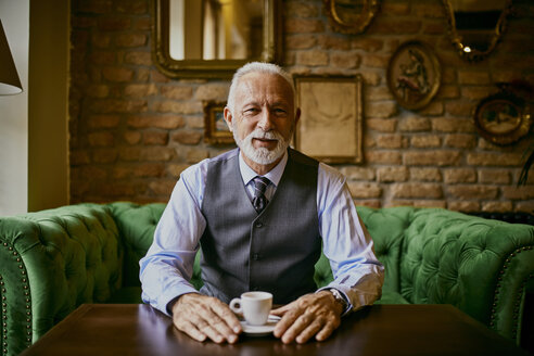 Portrait of elegant senior man sitting on couch in a cafe - ZEDF01107