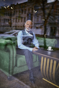 Elegant senior man sitting on couch in a cafe looking out of window - ZEDF01110