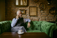 Elegant senior man sitting on couch in a cafe talking on cell phone - ZEDF01113