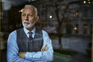 Elegant senior man looking out of window - ZEDF01116