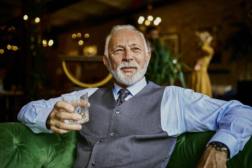 Portrait of elegant senior man sitting on couch in a bar holding tumbler - ZEDF01119