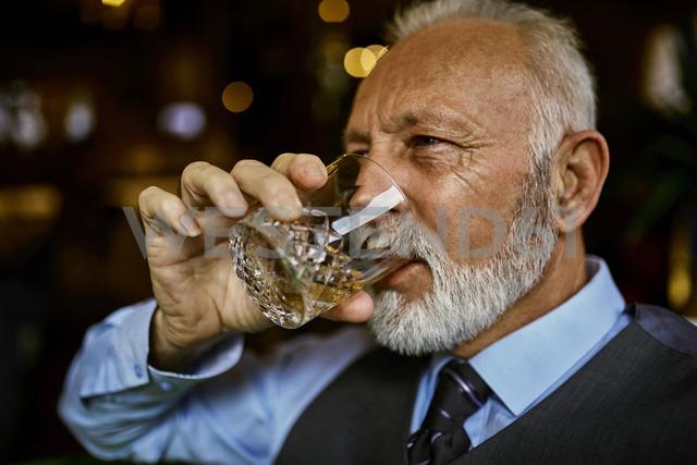 Portrait of elegant senior man drinking from tumbler - ZEDF01122