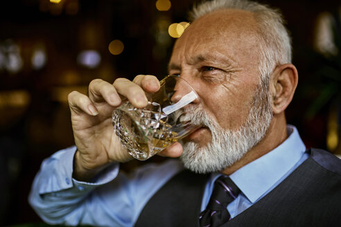 Portrait of elegant senior man drinking from tumbler - ZEDF01122