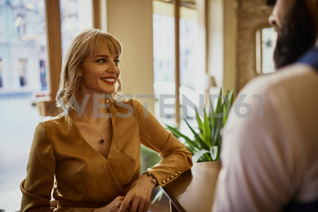Elegant smiling woman with man in a bar - ZEDF01125