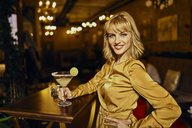 Portrait of elegant woman with cocktail in a bar - ZEDF01137