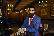 Portrait of elegant young man in a bar with tumbler - ZEDF01140
