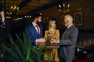 Two elegant men and woman socializing in a bar - ZEDF01146