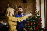Elegant couple decorating Christmas tree - ZEDF01152