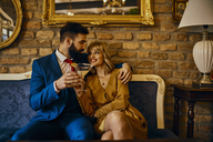 Happy elegant couple with drinks sitting on couch embracing - ZEDF01164