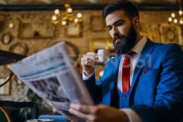 Elegant man drinking coffee and reading newspaper in a cafe - ZEDF01176