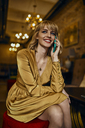 Portrait of smiling elegant woman in a bar on cell phone - ZEDF01179