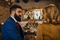 Elegant couple smiling at each other in a bar - ZEDF01182