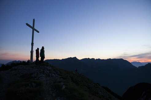 Austria, Tyrol, two hikers standing at summit cross - FAF00077