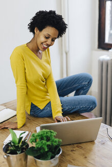 Young woman at home surfing the net, using laptop - GIOF03792