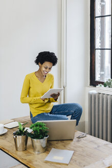 Young woman at home surfing the net, using digital tablet - GIOF03795