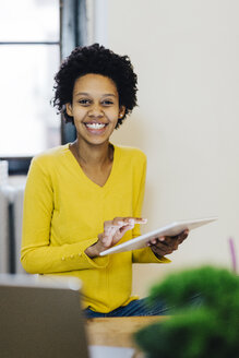 Happy young woman using digital tablet - GIOF03807