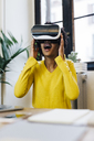 Laughing young woman playing game, wearing virtual reality goggles - GIOF03813