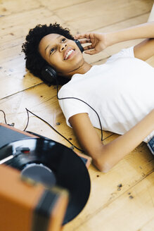 Young woman at home listening vinyl records, lying on ground - GIOF03828