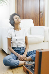 Young woman sitting on grounf listening music from record player, using headphones - GIOF03831